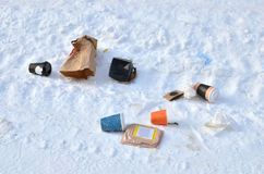 Afternoon people throw bags and containers from food to the street. The problem of environmental pollution. The problem of human nutrition. Garbage in the snow stock image