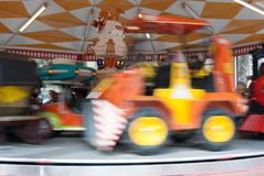 Tractor on carousel in movement. Afternoon at the playground games with the family Stock Image