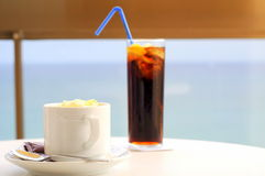 Afternoon refreshments (cafe and cola). Afternoon refreshments: a cup of warm cappuccino and a glass of cold cola stock images