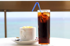 Afternoon refreshments (coke & coffee). Afternoon refreshments: a cup of warm cappuccino and a glass of cold cola royalty free stock photography