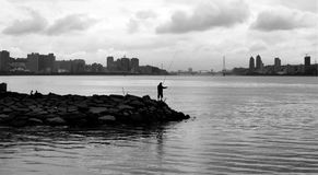 Afternoon Rock Fishing at the Fisherman`s Wharf. A black and white photo of a man standing in the foreground rock fishing on a sunny afternoon at Fisherman`s Royalty Free Stock Photography