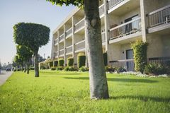 Afternoon shot of trees, grass field and apartment with balcony. At Los Angeles Stock Photo