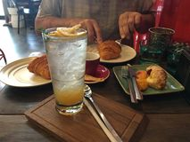 Afternoon snack in a cafe in Bangkok with coffee and lemon tea and croissant and cakes Royalty Free Stock Photo