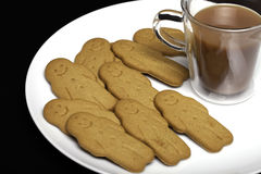 Afternoon snack comfort food. Gingerbread men biscuits and a cup Stock Photo
