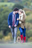 Afternoon stroll with the dog. Young couple walking together on a rainy day with their pet dog. They have their heads together and are holding hands Royalty Free Stock Photo