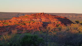 Afternoon sun on rocky knoll. Late afternoon sun over Australian outback rocky knoll with bird of pray on lookout. Long shadows and amazing colours Royalty Free Stock Photo