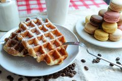 Afternoon tea. Belgain waffle and macarons with a cup of coffee Royalty Free Stock Photos