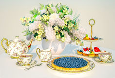 Afternoon tea. Bilberry pie, fruit cakes, tea, bouquet of flowers are located on a cloth. Royalty Free Stock Photos