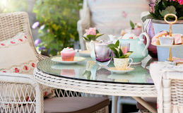 Afternoon tea and cakes in the garden. Afternoon tea and cakes in an English garden with cream wicker outdoor furniture stock images