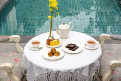 Afternoon tea with cup of tea and teapot and cake. On the table Stock Photos