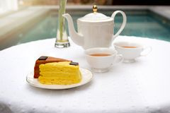 Afternoon tea with cup of tea and teapot and cake. On the table Royalty Free Stock Photography