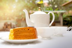 Afternoon tea with cup of tea and teapot and cake. On the table Royalty Free Stock Images