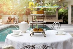 Afternoon tea with cup of tea and teapot on table with cake. By swimming pool Royalty Free Stock Image