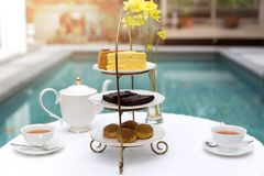 Afternoon tea with cup of tea and teapot on table with cake. By swimming pool stock photography
