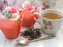 Afternoon tea with flowers cupcakes, vintage teacup, old silver spoon and petals brew on shabby table, tender colors of spring. Afternoon tea with flowers royalty free stock photography
