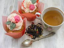 Afternoon tea with flowers cupcakes in vintage teacup, old silver spoon and petals brew on shabby table flat wiev. Afternoon tea with flowers cupcakes in vintage stock photography
