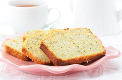Afternoon tea. Lemon poppyseed loaf slices with cup of tea in horizontal format Stock Photos