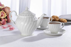 Afternoon Tea. Teapot and teacups on white tablecloth against backlit white curtain with biscuits and flowers in background Royalty Free Stock Images