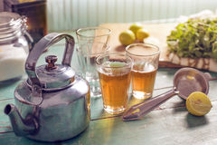Afternoon tea time. Steamy hot black tea in two chai glasses, a vintage tea kettle, tea strainer,lemons mint leaves , kept on a vintage looking kitchen table on Royalty Free Stock Photos