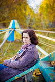 Afternoon Walk. Woman sitting on an old carrousel in an autumn park. With copy space Royalty Free Stock Photography