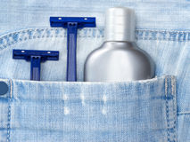 Aftershave lotion and disposable razors in blue jeans pocket. Aftershave lotion and disposable razors in shabby pocket of blue jeans. Shaving cosmetic products stock photography