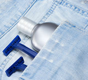 Aftershave lotion and disposable razors in blue jeans pocket. Aftershave lotion and disposable razors in shabby blue jeans pocket. Shaving cosmetic products and royalty free stock images