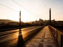 Afton på Manes Bridge med konturn av den Prague slotten Royaltyfri Foto