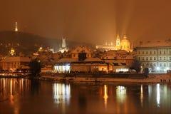 Afton romantiska snöig Prague Lesser Town ovanför floden Vltava med kullen Petrin, Tjeckien Royaltyfri Bild