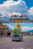 Afton, Wyoming, United States - June 07, 2018: The world`s larges elkhorn arch at the entrance of the town, with cars on. The road and vehicles parked royalty free stock photography