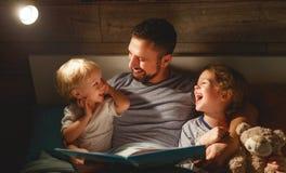 Aftonfamiljläsning fadern läser barn bok för goin arkivbilder