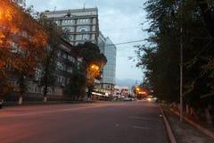 Aftongatan tänds av lyktor som träden hänger över vägen Arkivbild