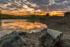 Aftonglöd av molnig himmel över River Valley med solnedgångreflexion i vatten Royaltyfria Bilder