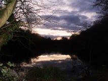 Aftonhimmel reflekterad i sjön arkivfoton