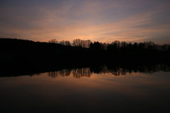 Aftonhimmelreflexion i en sjö, solnedgångbakgrund royaltyfria foton