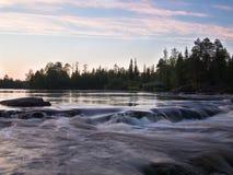 Aftonlandskap med flodstenar Arkivbild