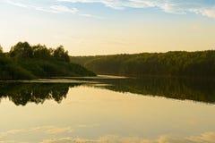 Aftonlandskap med sjön och skogsbevuxna kuster arkivbild