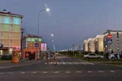 Aftonljus på trottoarerna och belysningen av byggnader in Arkivbild