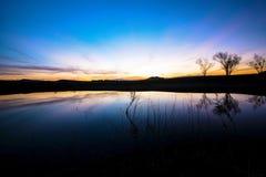 Aftonljus som reflekterar av sjön efter solnedgång Arkivfoton