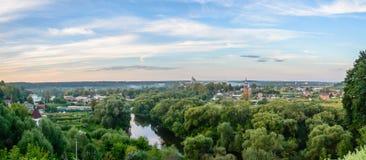 Aftonpanorama av den ryska staden med en flod och kyrkor arkivfoton