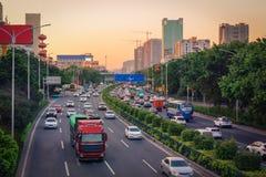 Aftonrusningstid i storstaden, trafikstockning från många bilar på väg med skilda vägbanorvägen, upptagen stads- sikt på solnedgå royaltyfri bild