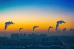 Aftonsikt av det industriella landskapet av staden med rökutsläpp från lampglas på solnedgången Fotografering för Bildbyråer