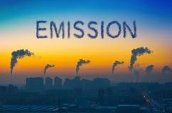 Aftonsikt av det industriella landskapet av staden med rökutsläpp från lampglas på solnedgången Arkivbild