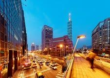 Aftonsikt av en fot- spång över ett hörn för upptagen gata i den Taipei staden med det Taipei 101 tornet & World Trade Center Royaltyfria Bilder
