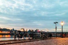 Aftonsikt av parkerade cyklar tillsammans med den holländska floden Maas Fotografering för Bildbyråer