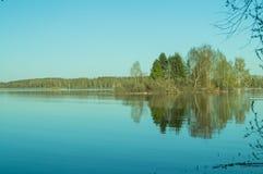 Aftonsikt av sjön med reflexion av träd i vattnet Royaltyfria Bilder