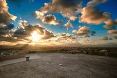 Aftonsikt från observationsdäcket av den Santa Barbara slotten till staden och solen i molnen bak bergen Alicant royaltyfri fotografi