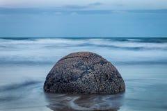 Aftonsikten av den perfekta sfäriska stenen på Moeraki stenblock sätter på land royaltyfria foton