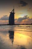 Aftonsol som reflekterar Burj Al Arab på stranden Fotografering för Bildbyråer