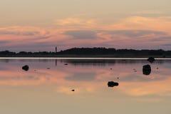 Aftonsolljus, fyr och vaggar på kusthimmelreflexion på vatten sommar för berg för strandkustlinjehorisont Naturlig miljö för sjös royaltyfri fotografi