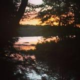 Aftonsolnedgång reflekterad på sjön arkivbild